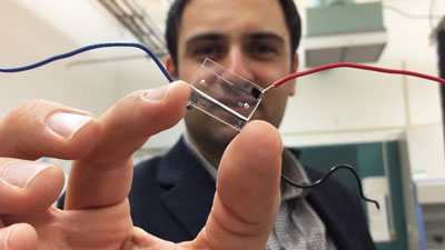 Image: A hybrid microfluidic chip (held by Dr. Fatih Sarioglu) uses a simple circuit pattern to assign a unique seven-bit digital identification number to each cell passing through the channels (Photo courtesy of the Georgia Institute of Technology).